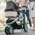 cropped mother and father pushing bugaboo fox stroller