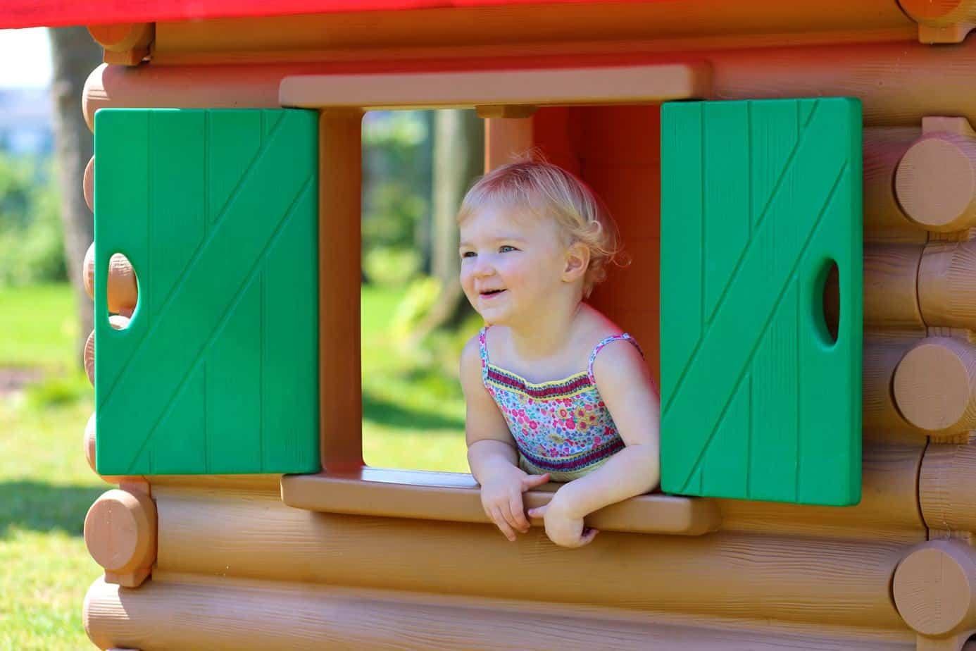 cute toddler girl playing in playhouse