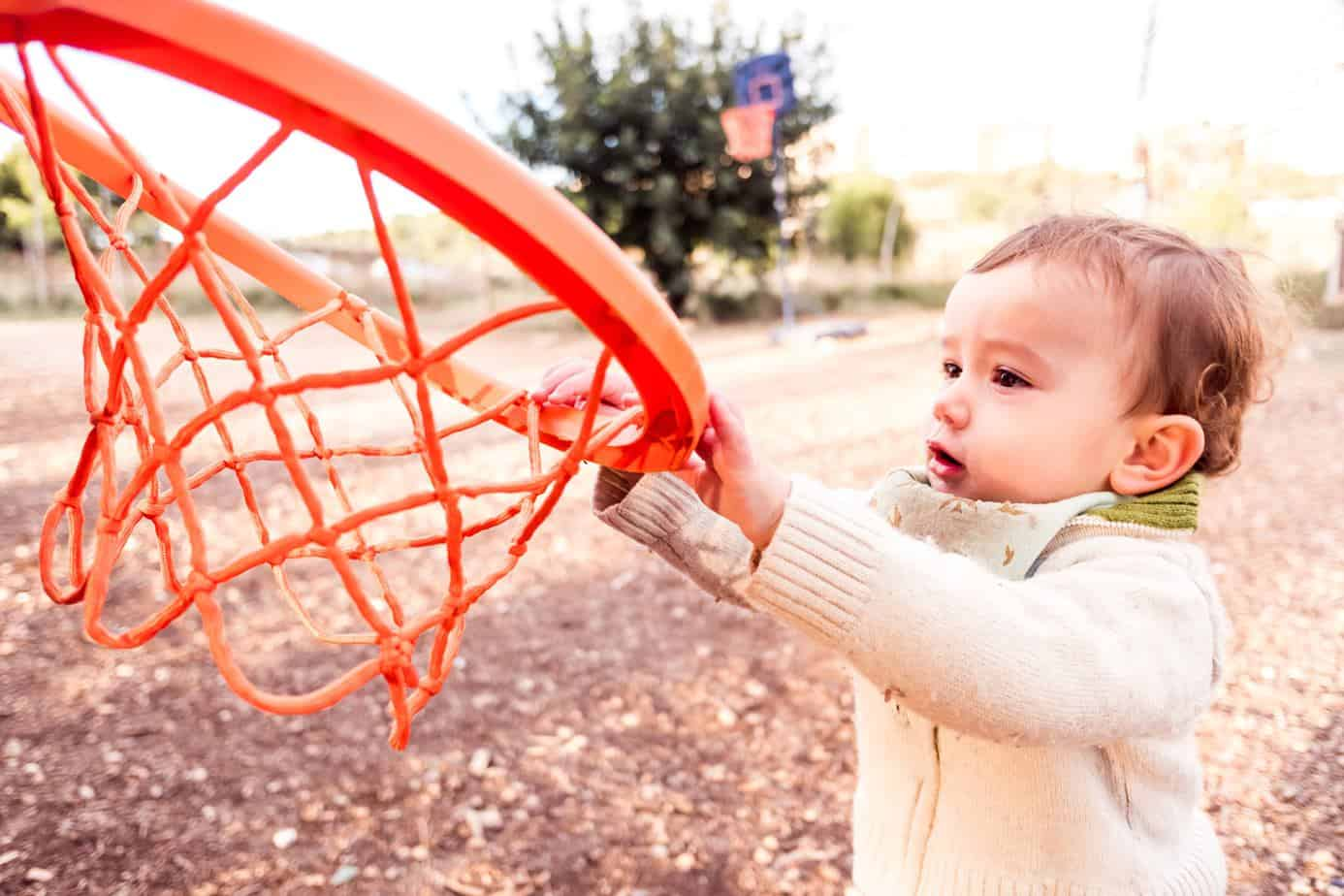 cute toddler reaching basketball hoop