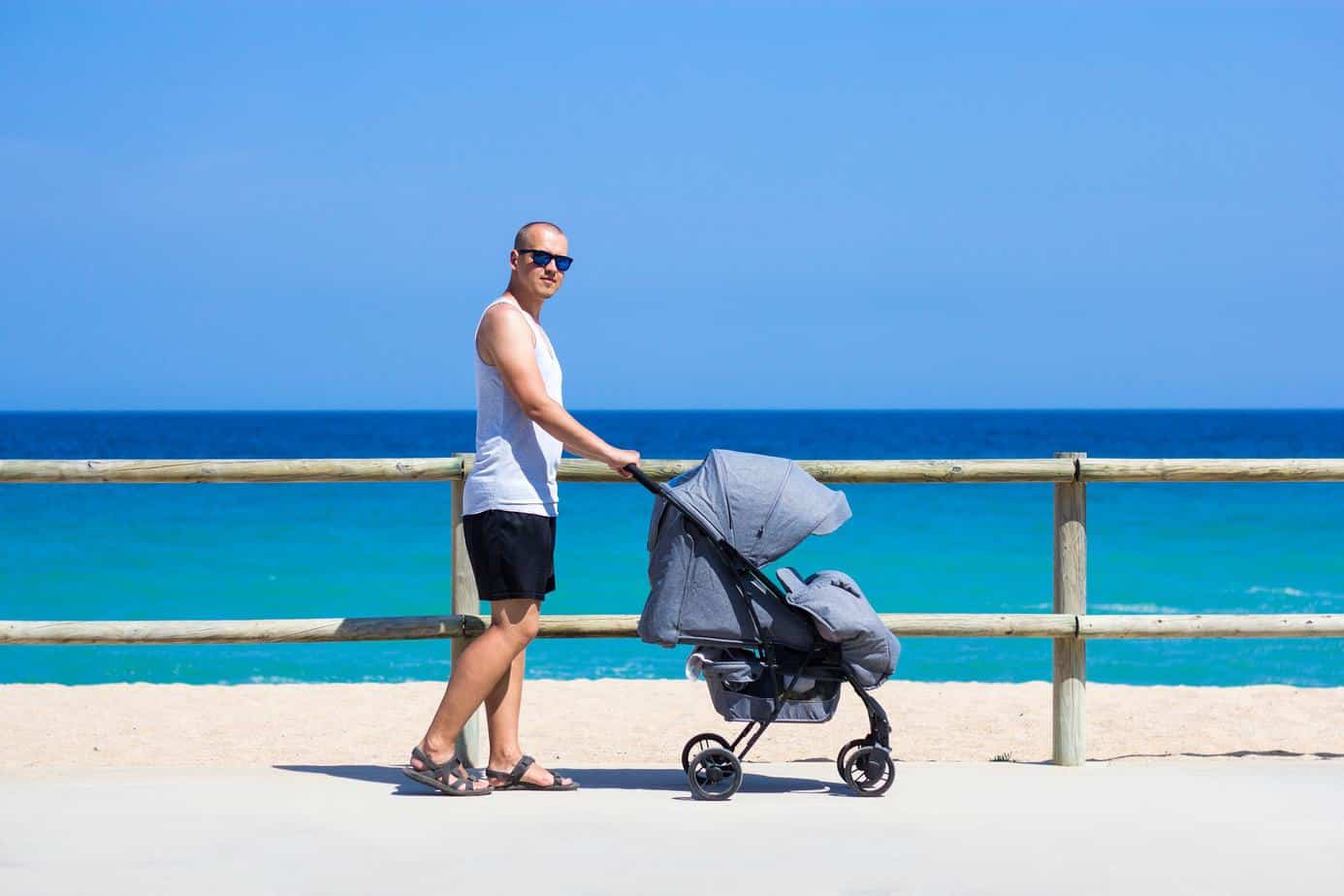father pushing chicco viaro travel system baby stroller in the beach