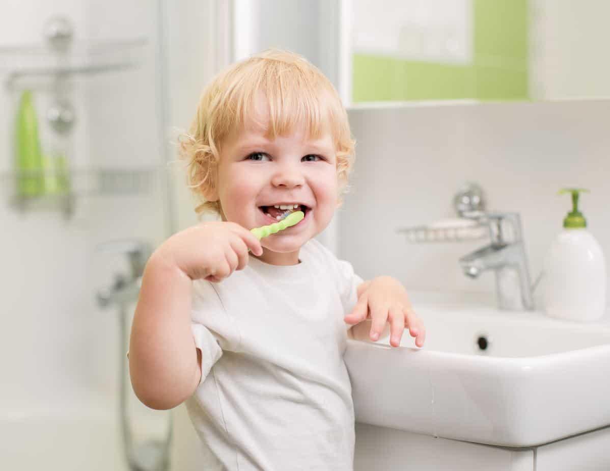 toddler brushing teeth inside the bathroom