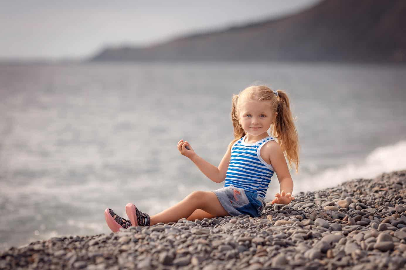 toddler sitting in the beach wearing water shoes