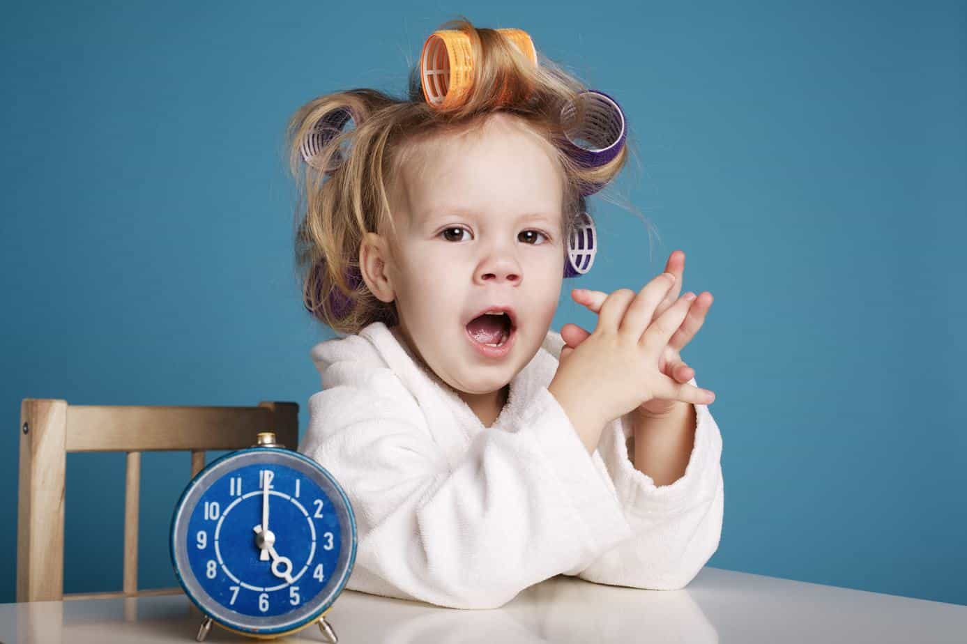 toddler sitting while yawning with alarm clock on table