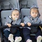 twin baby sitting in schwinn double jogging stroller